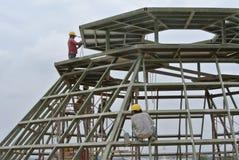 Travailleurs de la construction rectifiant la surface métallique Image stock
