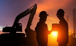 Travailleurs de la construction travaillant à un chantier de construction au coucher du soleil pour le fond d'industrie Photos stock