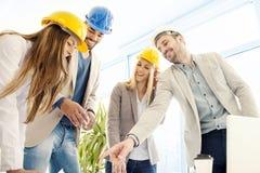 Travailleurs de la construction vérifiant les plans architecturaux avant Photo libre de droits