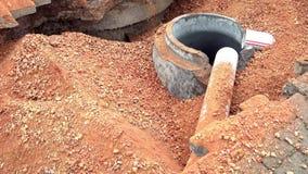 Travailleurs de la construction versant le sol dans le puits utilisant des pelles clips vidéos