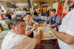Travailleurs de marché de nourriture ayant l'amusement pendant une coupure et jouant un jeu de société - dominos Image libre de droits