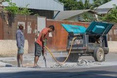 Travailleurs de route cassant la rue Image libre de droits