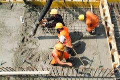 Travailleurs de rue versant le ciment avec une pompe dans un constru de route Image stock