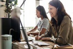 Travailleurs de service client s'asseyant devant le travail d'ordinateurs photos stock