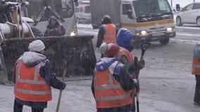 Travailleurs de service collectif dégageant la neige et la glace de la route banque de vidéos