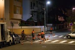 Travailleurs de service d'entretien des routes peignant le zèbre la nuit photo stock