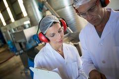 Travailleurs discutant dans l'usine d'huile photo stock