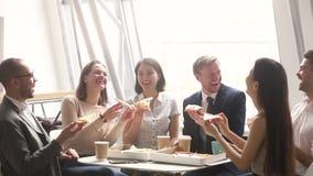 Travailleurs divers gais de société de personnes d'équipe riant mangeant de la pizza ensemble banque de vidéos