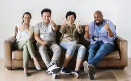 Travailleurs divers s'asseyant ensemble et montrant le pouce sur le divan Photo libre de droits