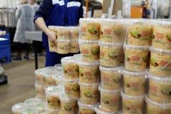 Travailleurs empilant des récipients avec le chou mariné dans une usine de traitement des denrées alimentaires des produits alime photos stock