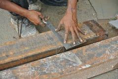 Travailleurs employant la règle en acier de 90 degrés pour mesurer l'acier doux Image libre de droits