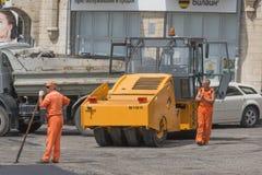 Travailleurs et rouleau d'asphalte, réparation de route Photos stock