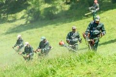 Travailleurs fauchant l'herbe dans le printemps en parc public des jeunesse image libre de droits