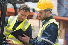 Travailleurs focalisés d'entrepôt parlant ensemble images stock