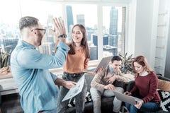 Travailleurs heureux satisfaisants ayant l'amusement et la position dans la chambre Photo stock