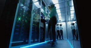 Travailleurs informatiques au centre de traitement des données rougeoyant clips vidéos