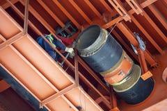 Travailleurs installant le réseau de pipe-lines de chauffage urbain sous le métal photographie stock libre de droits