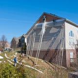 Travailleurs installant les panneaux de voie de garage en plastique sur la maison de deux histoires. Images stock
