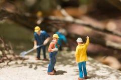 Travailleurs miniatures dégageant les arbres tombés Photographie stock