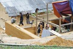 Travailleurs non identifiés construisant une maison avec de l'argile et des pierres le 7 décembre 2011 dans le secteur montagneux  Images libres de droits