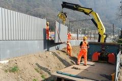 Travailleurs pendant l'installation des barrières de bruit sur le chemin de fer photographie stock libre de droits