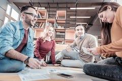 Travailleurs réfléchis joyeux reposant et discutant des idées Photo stock