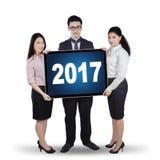 Travailleurs se tenant avec 2017 sur le panneau d'affichage Photo stock