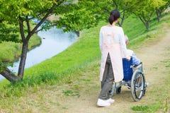 Travailleurs sociaux et aîné japonais dans le domaine Photos stock