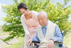 Travailleurs sociaux et aîné japonais dans le travailleur social de champ Photographie stock libre de droits