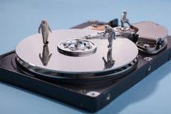 Travailleurs sur le disque d'unité de disque dur - concept informatique de sécurité Photo libre de droits