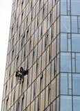 Travailleurs suspendus sur des cordes réparant le bâtiment en verre Photos stock