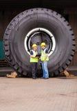 Travailleurs tenant le pneu Image libre de droits