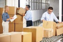 Travailleurs vérifiant des marchandises sur la ceinture dans l'entrepôt de distribution Images libres de droits