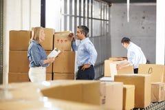 Travailleurs vérifiant des marchandises sur la ceinture dans l'entrepôt de distribution photographie stock libre de droits