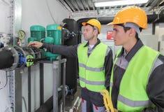 Travailleurs vérifiant des paramètres de pression Images stock