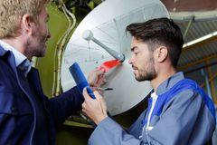 Travailleurs vérifiant une antenne images libres de droits