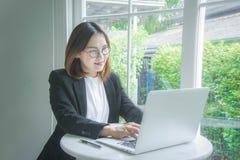 Travailleuse active, jeune sourire asiatique et hasard de style de femme d'affaires Image libre de droits
