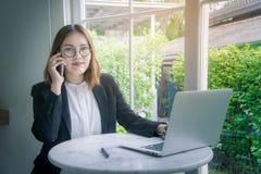 Travailleuse active, jeune style asiatique de femme d'affaires parlant sur smar Photo stock