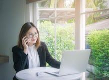 Travailleuse active, jeune style asiatique de femme d'affaires parlant sur smar Photos libres de droits