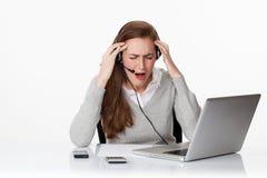 Travailleuse active 20s désespérée sous le choc avec le casque et l'ordinateur Photos stock