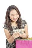 Travailleuse active souriant tenant l'argent liquide, rêvant et recherchant plus de Photo stock