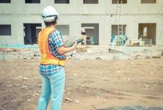 Travailleuse et ingénieur asiatiques sur le chantier utilisant le comprimé pour vérifier l'exactitude dans les endroits devant le images libres de droits