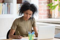 Travailleuse ou étudiant africaine travaillant avec l'ordinateur portable faisant des notes images libres de droits
