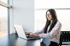 Travailleuse s'asseyant dans le bureau tout en à l'aide de l'ordinateur portable et dactylographiant par le clavier Image stock