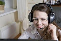 Travaillez comme employé avec des écouteurs se reposant dans la présidence dans le bureau. Photos libres de droits