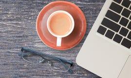Travaillez le bureau avec l'ordinateur portable et la tasse de café chaude Photographie stock libre de droits