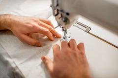 Travaillez le tissu de couture avec une machine à coudre à l'intérieur Image stock