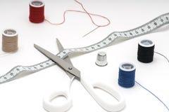 Travaillez les outils sur la table blanche avec les écheveaux rouges, bleus et noirs Image libre de droits