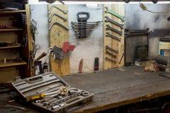 Travaillez les outils sur le mur de garage et la table de travail Photographie stock libre de droits