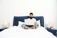 Travaillez qui le rend somnolent travail barbu de hippie d'homme sur l'ordinateur portable homme somnolent brutal dans la chambre photographie stock libre de droits